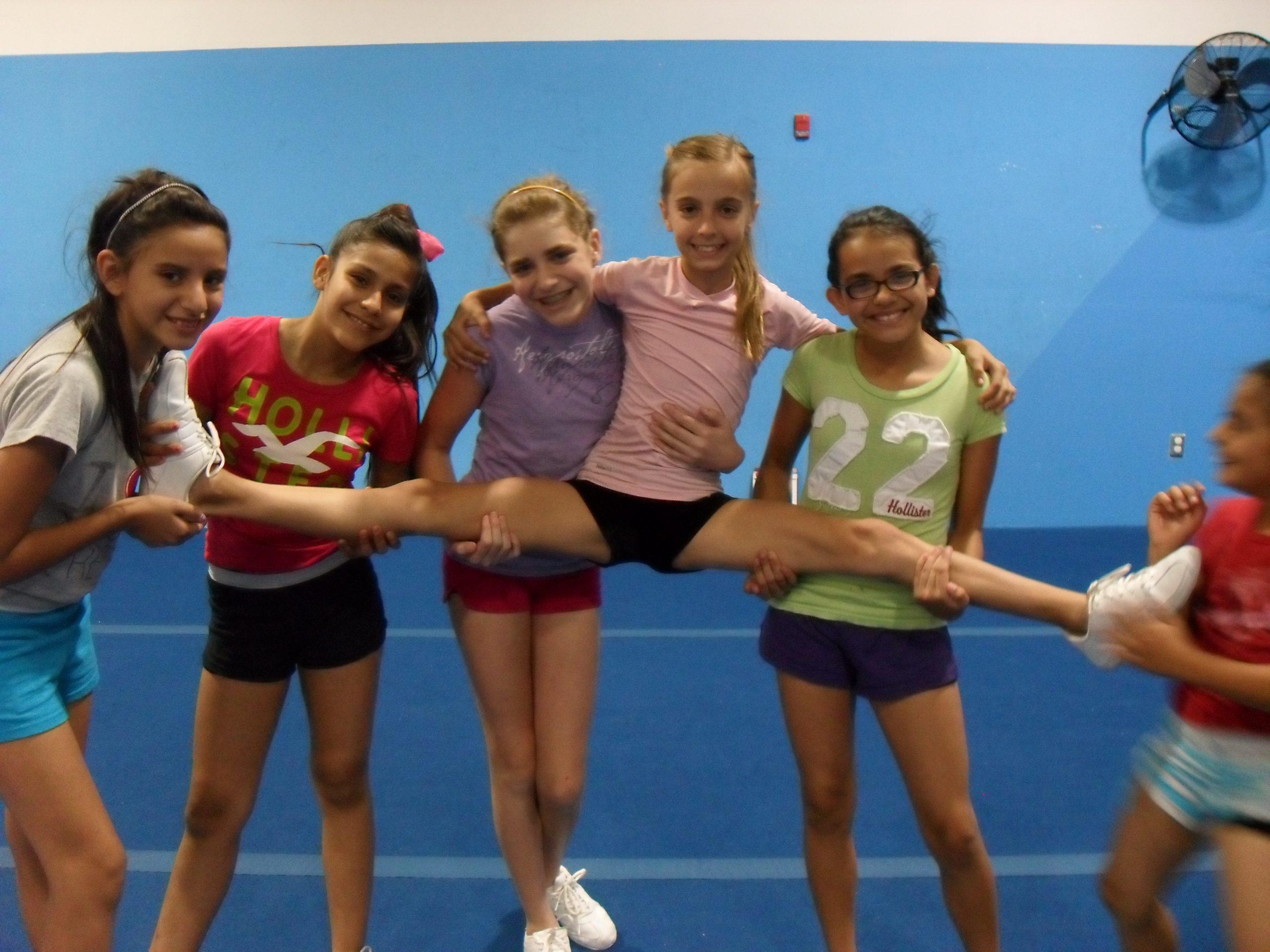 4 girls hold the 5th girl doing the splits