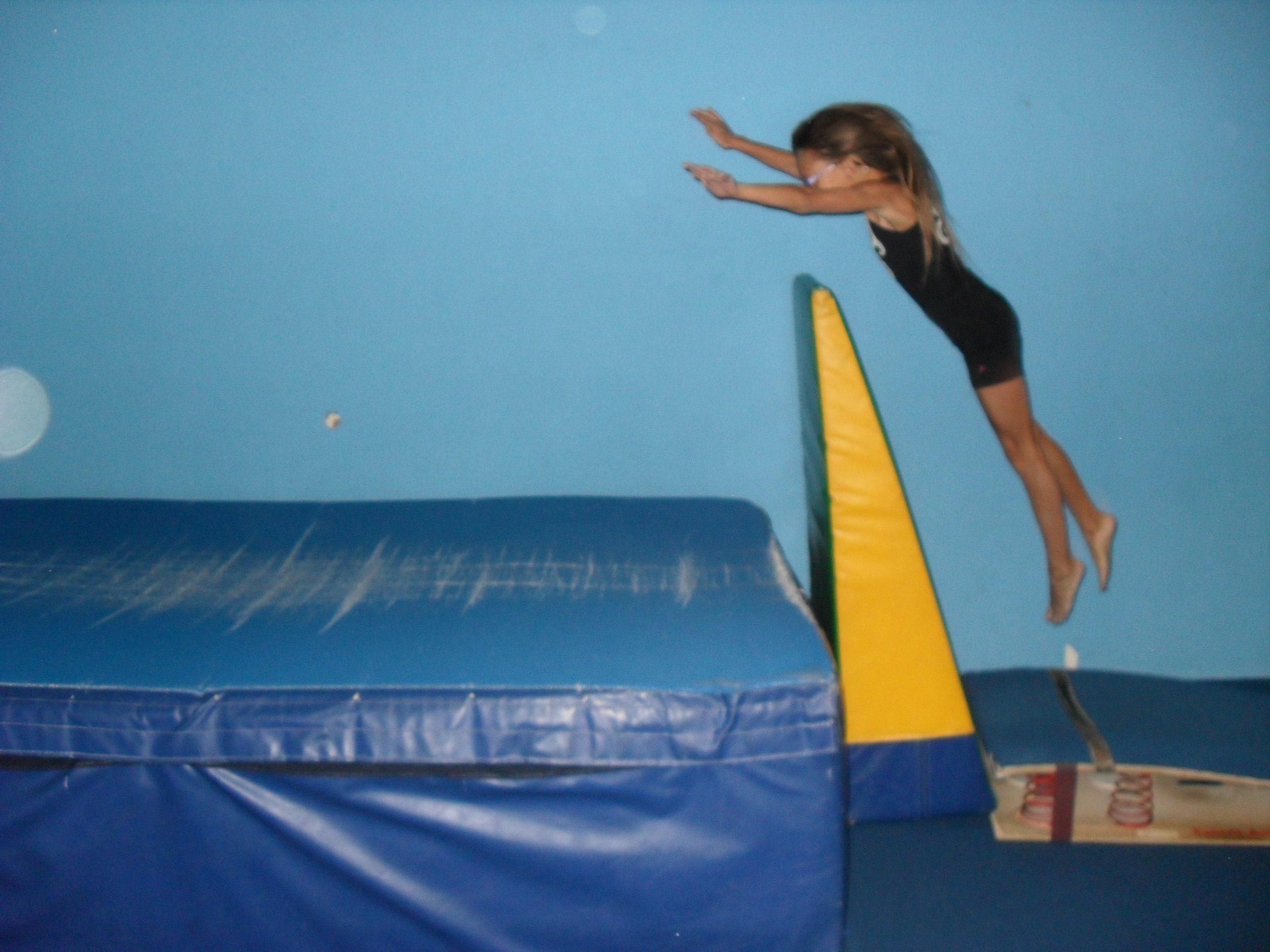 Girl Jumping over a wedge mat